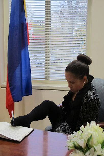 Jessica Cox, the world's first armless pilot, uses her foot to sign the Book of Condolences for victims of Typhoon Haiyan at the Philippine Embassy. (Embassy Photo by Elmer G. Cato)