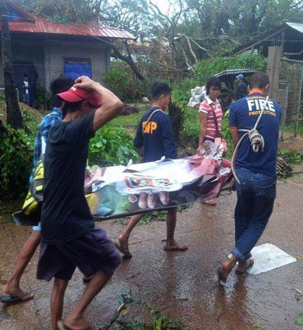 The body of a typhoon victim is carried by rescuers. Photo by Danny Pata, GMA News