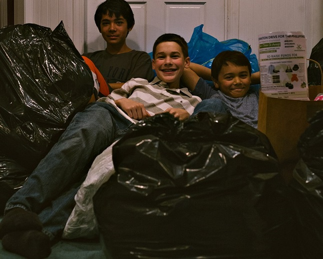 Exhausted but having fun, the boys crash on bags of clothes