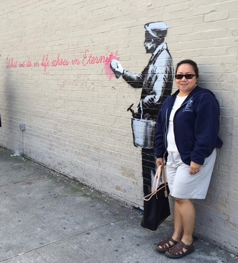 The author beside a Banksy graffiti: 'It's a maddening world out there.' Photo by Boyet Loverita