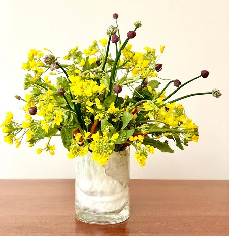 This arrangement uses broccoli rabe flowers, chives, mint, chilis, and cabbage.