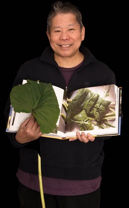 Dorotan's portrait at the ongoing exhibition, 'New Immigrants: What Gifts We Bring.' He is shown beaming with a taro leaf in his hand. Laing, taro leaves cooked with garlic, onion, and chili in coconut milk, is the quintessential Bicolano dish. Photo by Tom Pich