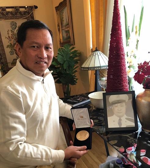 ANCOP USA Executive Director Roger Santos proudly shows his father's Congressional Gold Medal given to Filipino war veterans. The FilAm Photos