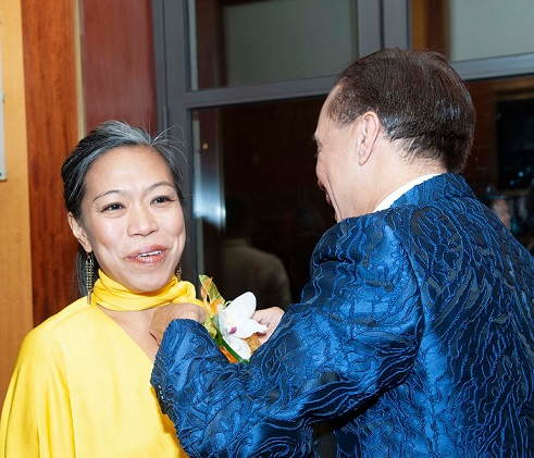 NYC Housing Commissioner Maria Torres Springer gets a corsage from TOFA supporter Erno Hormillosa.